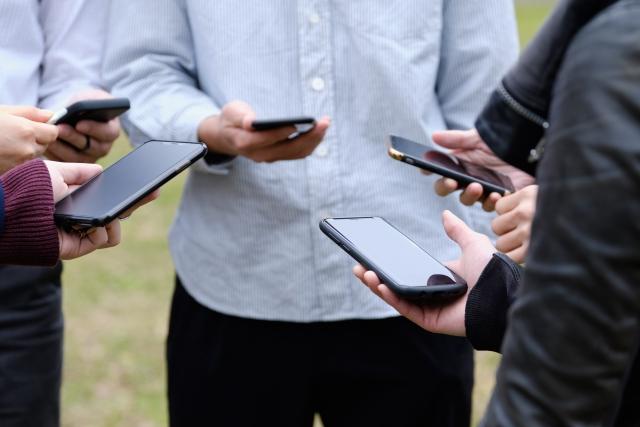 屋外でスマホゲーム・アドレス交換をする人々